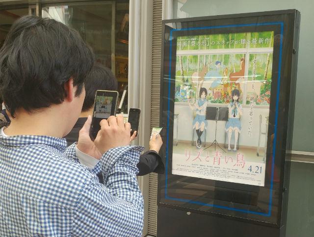 映画館で作品ポスターを撮影するファンの人たち